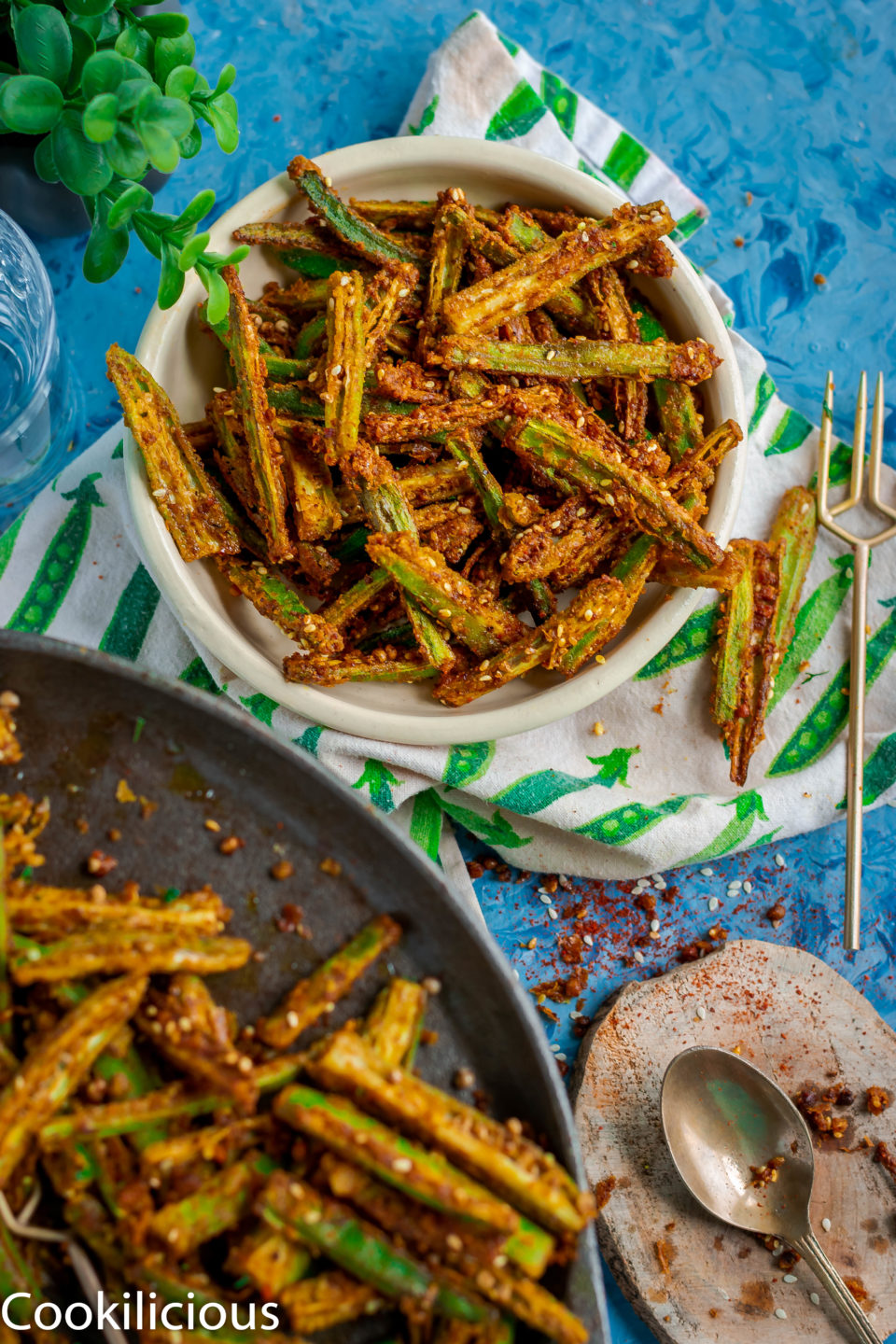a bowl of Kurkuri Masala Bhindi with a spoon on the side