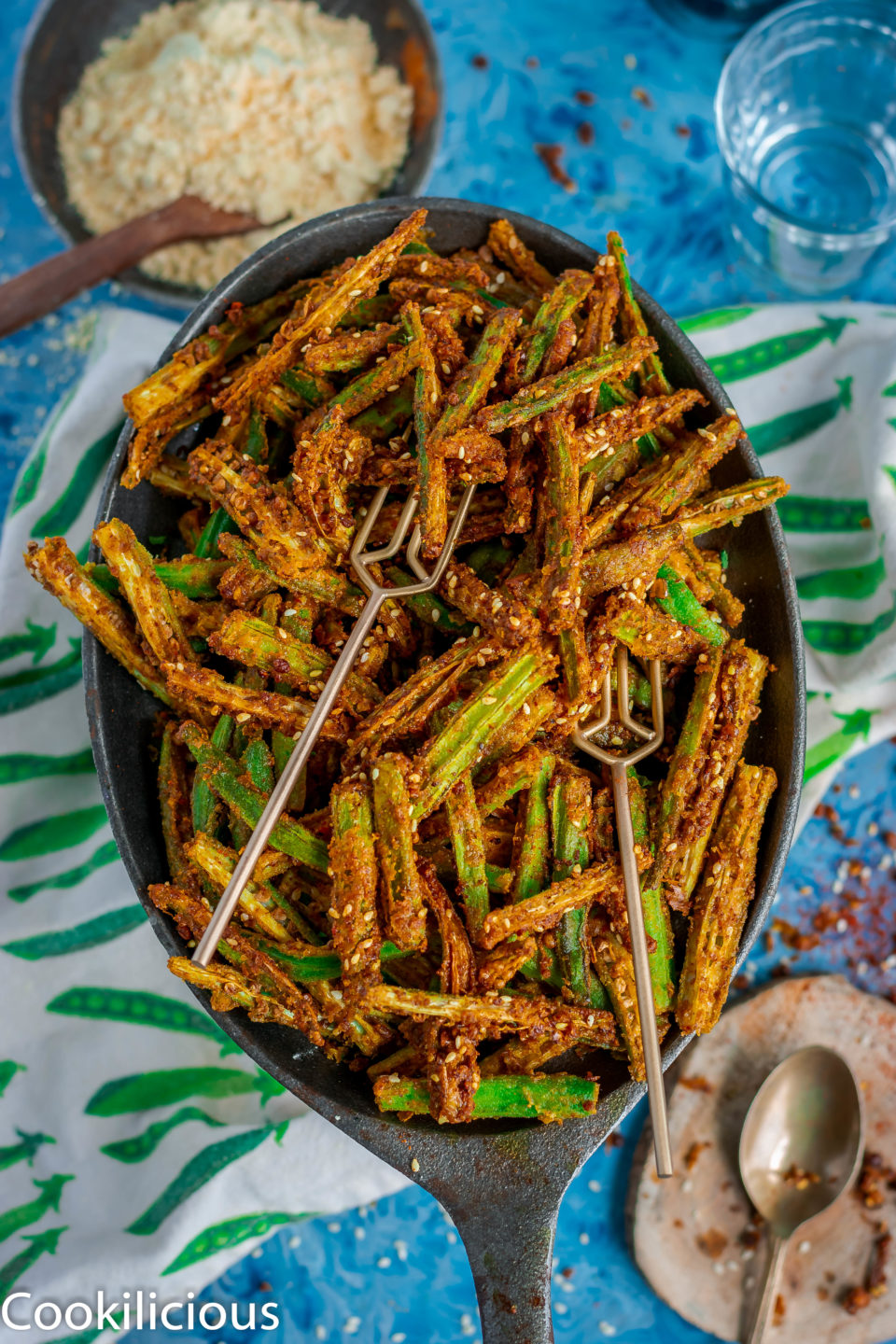 an oval platter filled with Kurkuri Masala Bhindi with 2 forks in it