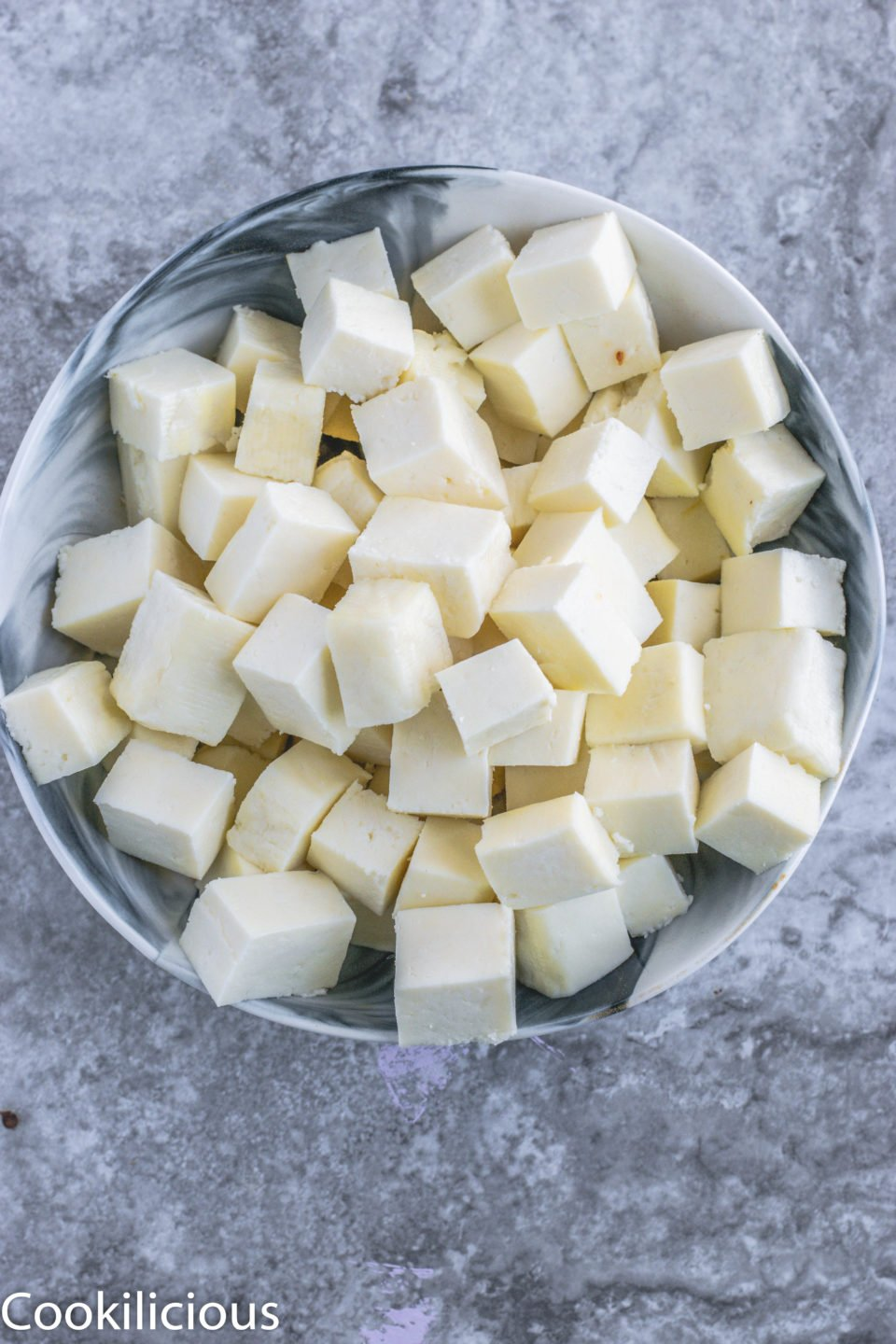 a bowl of cut paneer being used to make Achari Paneer