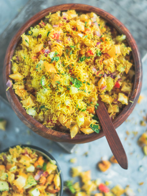 close up shot of 2 bowls containing Crispy & Masaledar Cheeselings Bhel with a spoon in it