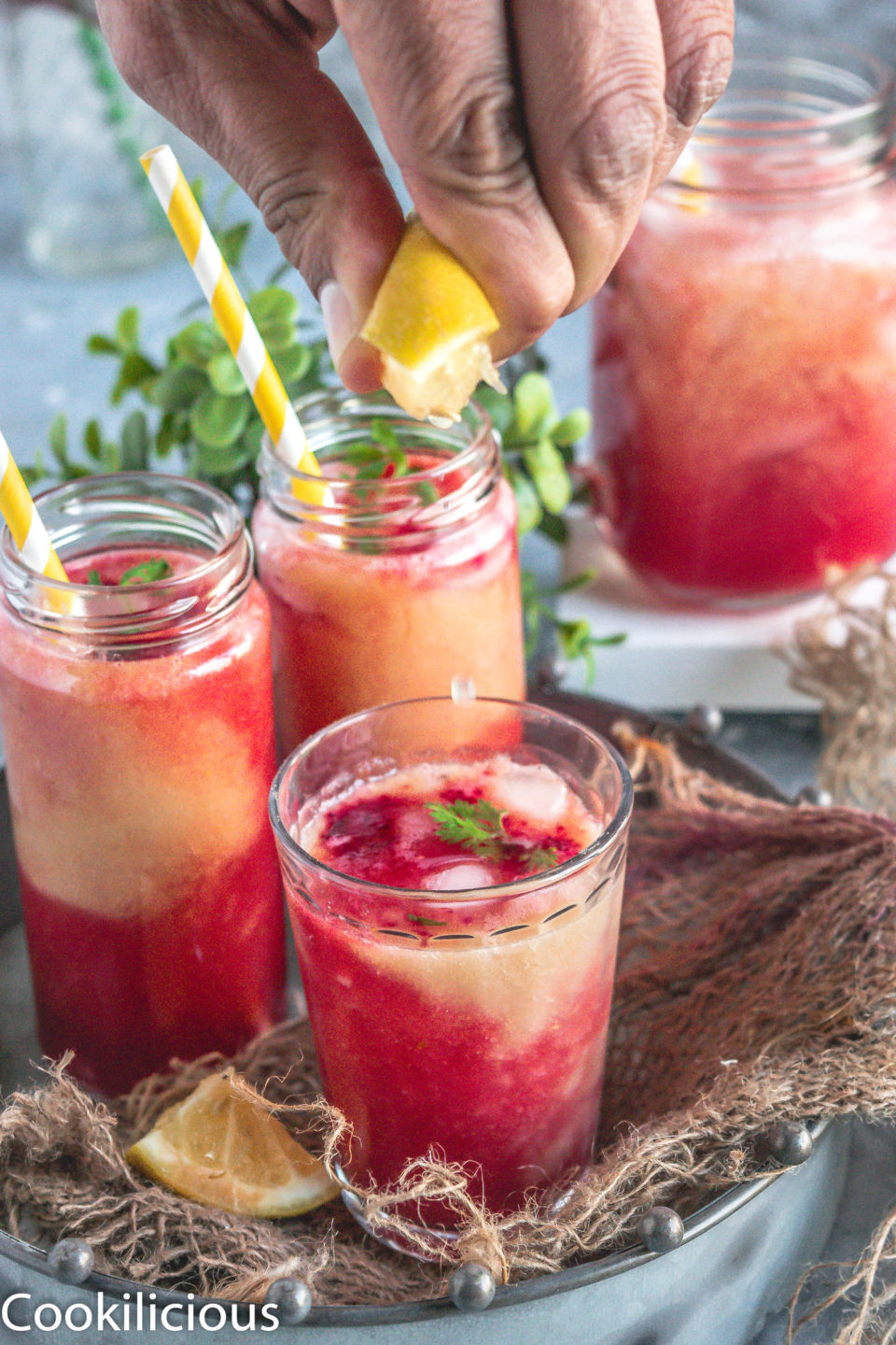 a hand squeezing lemon juice over a glass of Fresh Guava & Watermelon Non Boozy Summer Drink