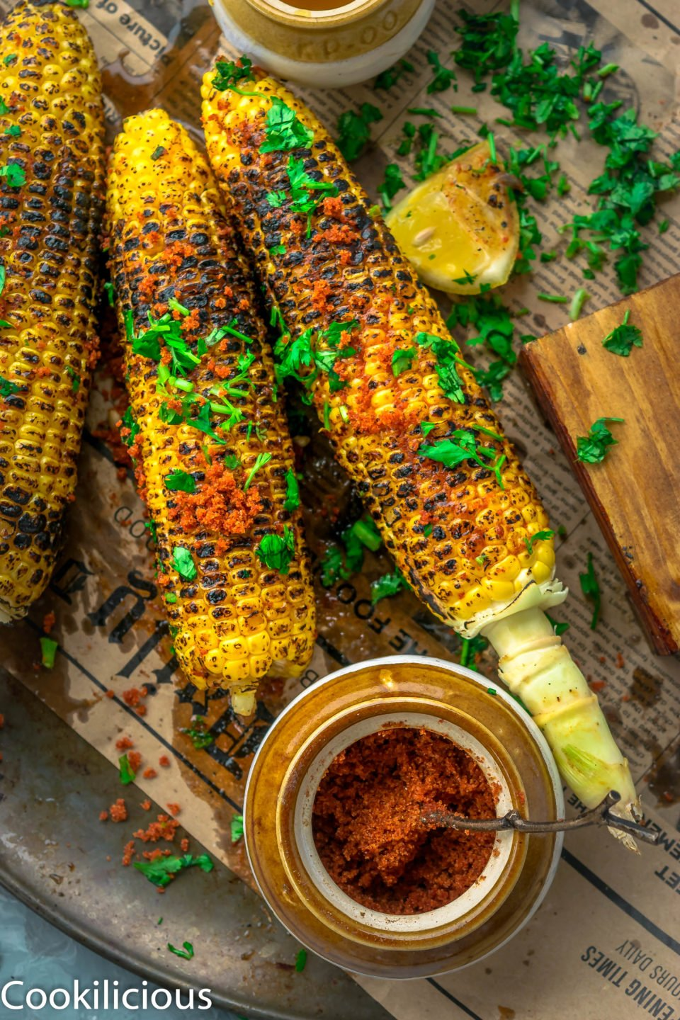 2 Indian Street Style Corn On The Cob on a platter with a bowl of spice rub on the side