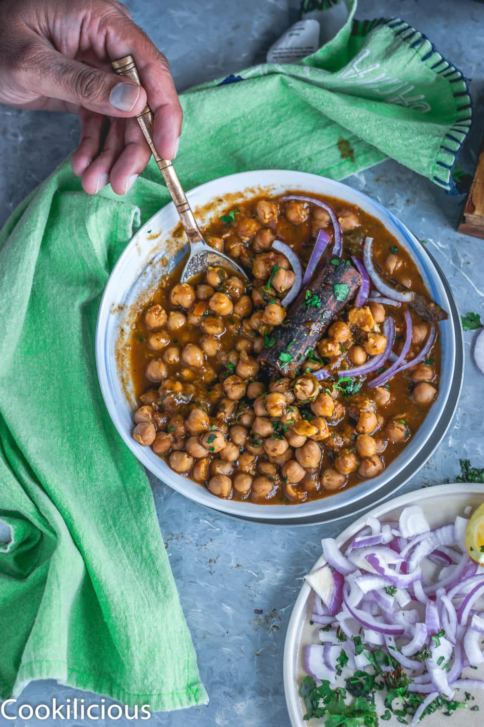 a hand with a spoon digging into a bowl of chana palak