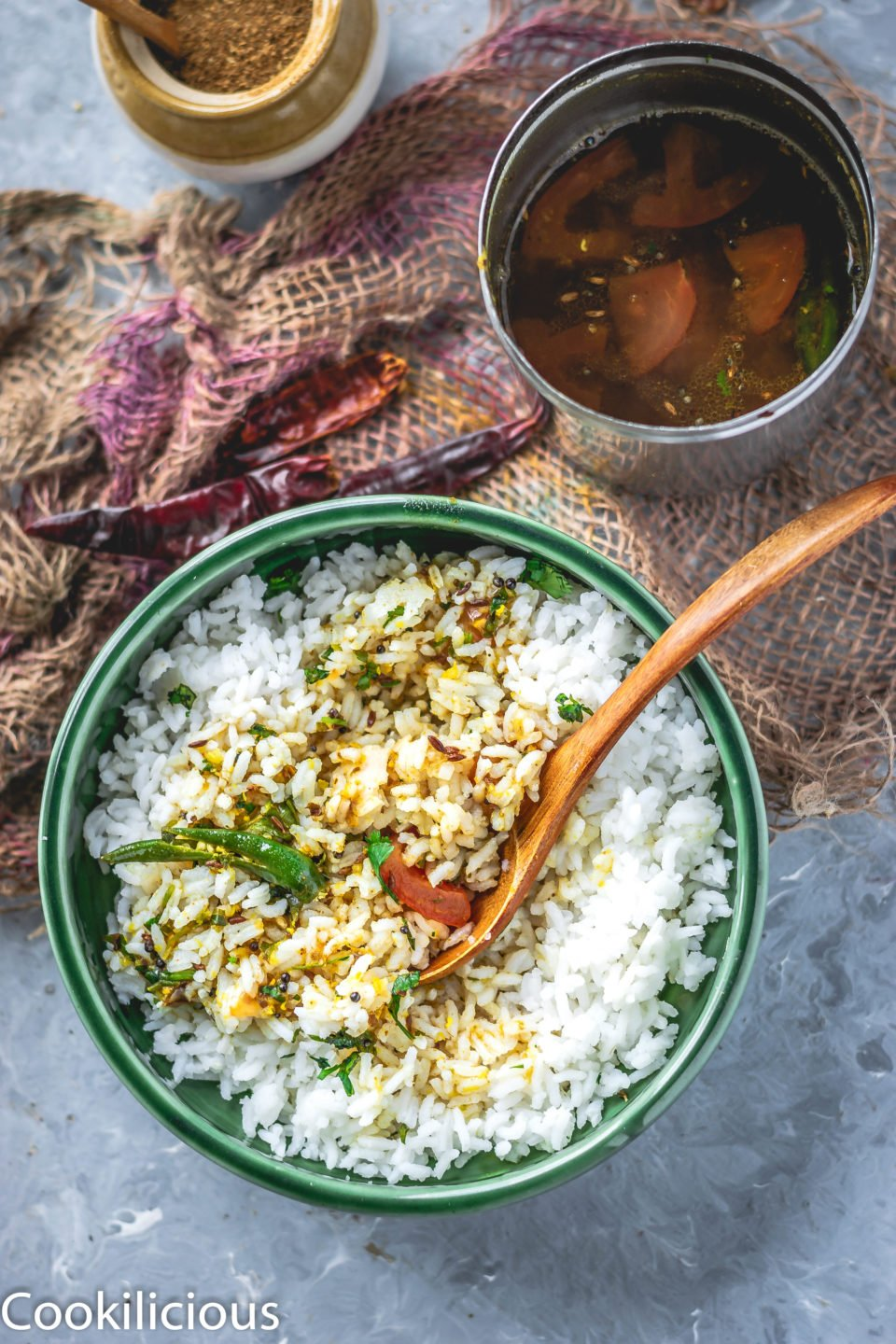 a bowl of South Indian Tomato Rasam With Pink Lentils with rice and vessel filled with rasam on the side