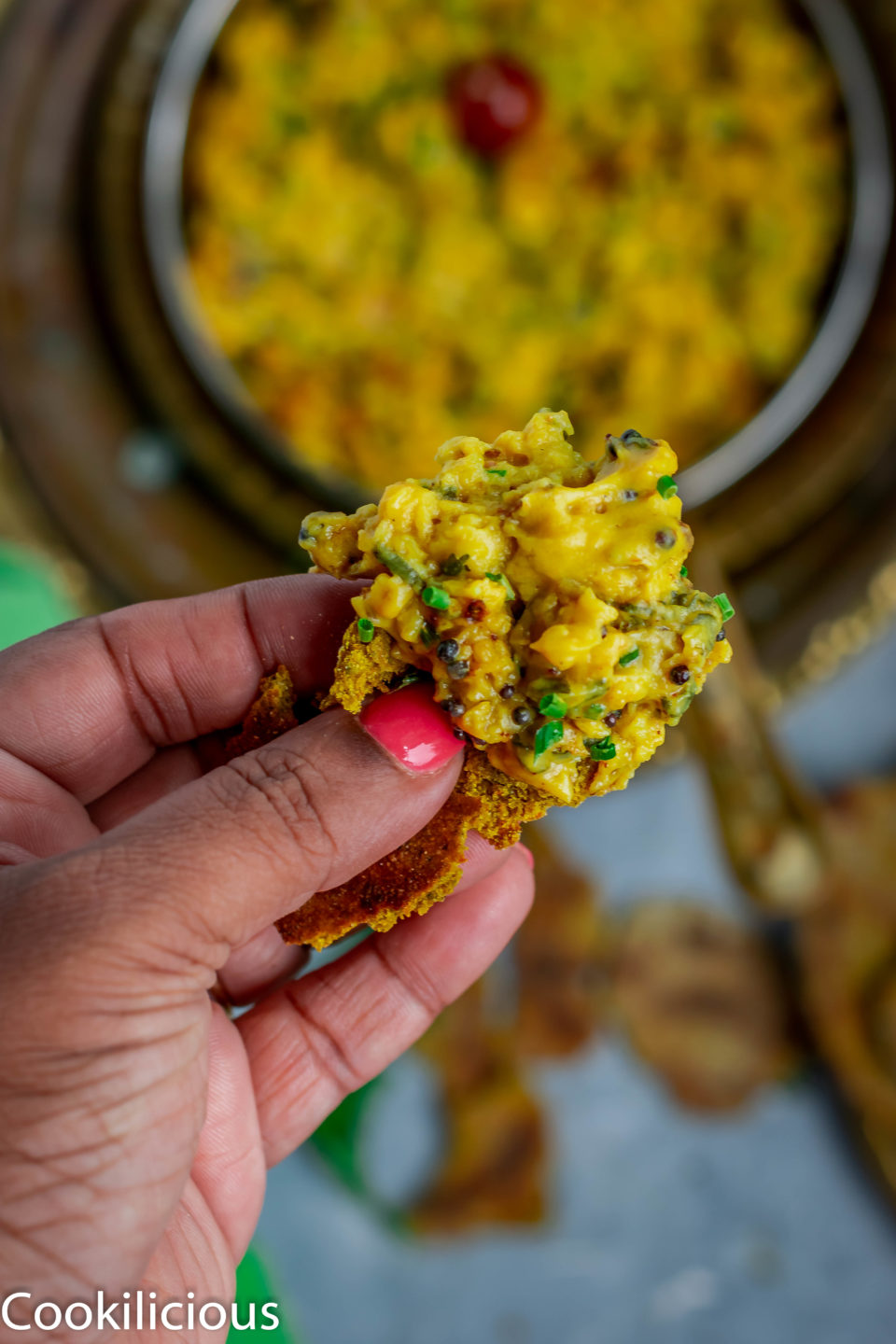 a hand holding a piece of bhakri with besan pitla