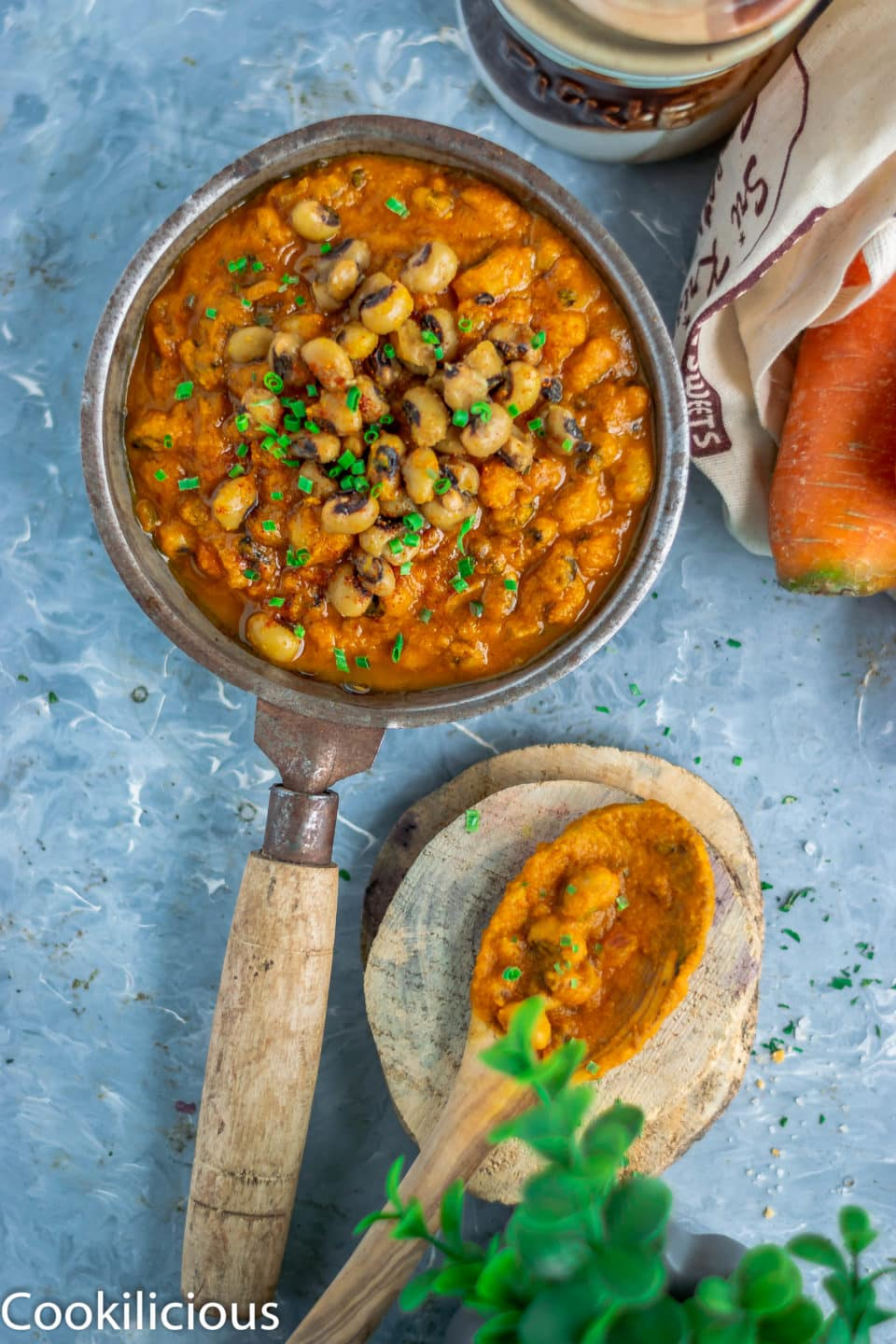 Lobia Ki Khatti Meethi Dal in a small pan and a wooden spoon resting on a wooden coaster next to it