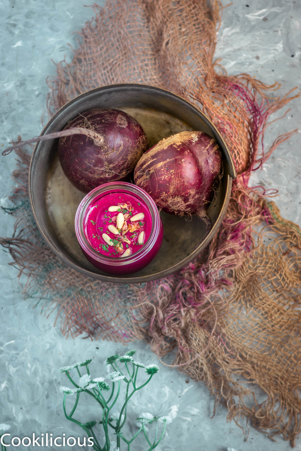 2 beets and a jar of beetroot pesto in a round tray