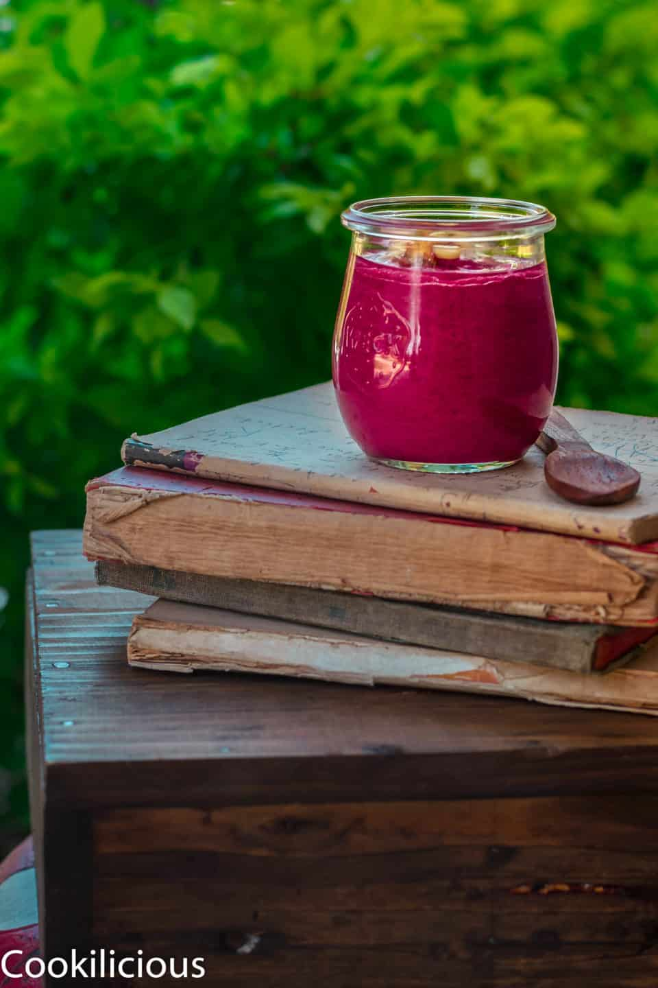 a jar of beetroot pesto placed over a pile of books in the outdoors