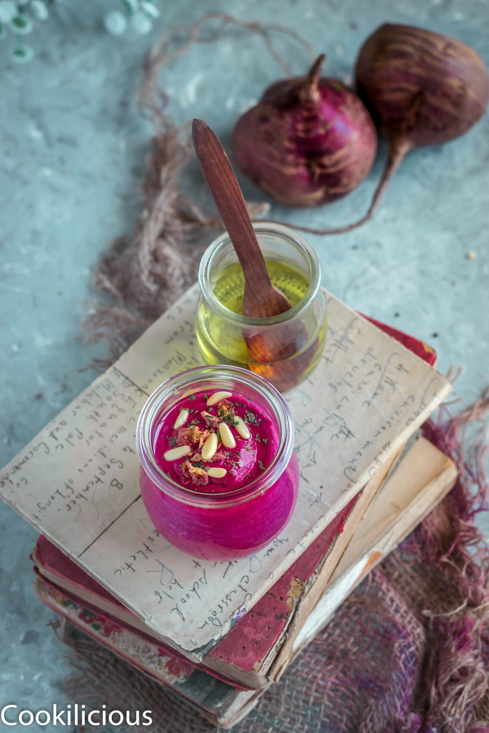 a jar of olive oil and beetroot pesto resting over a pile of books