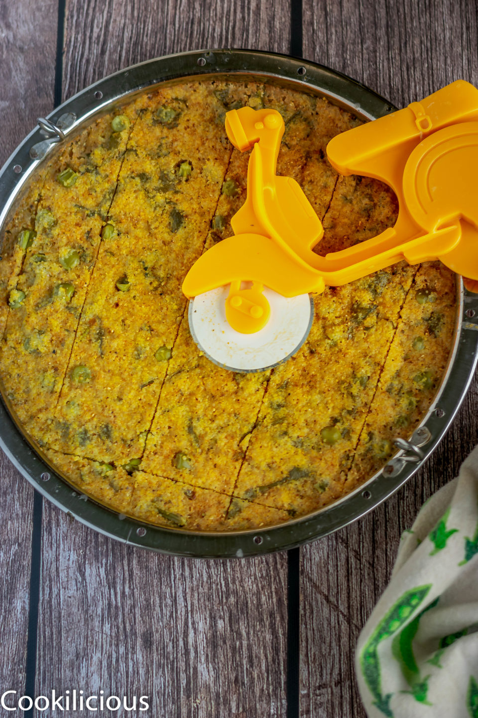 Corn Dhokla in a tray with a pizza cutter on top of it