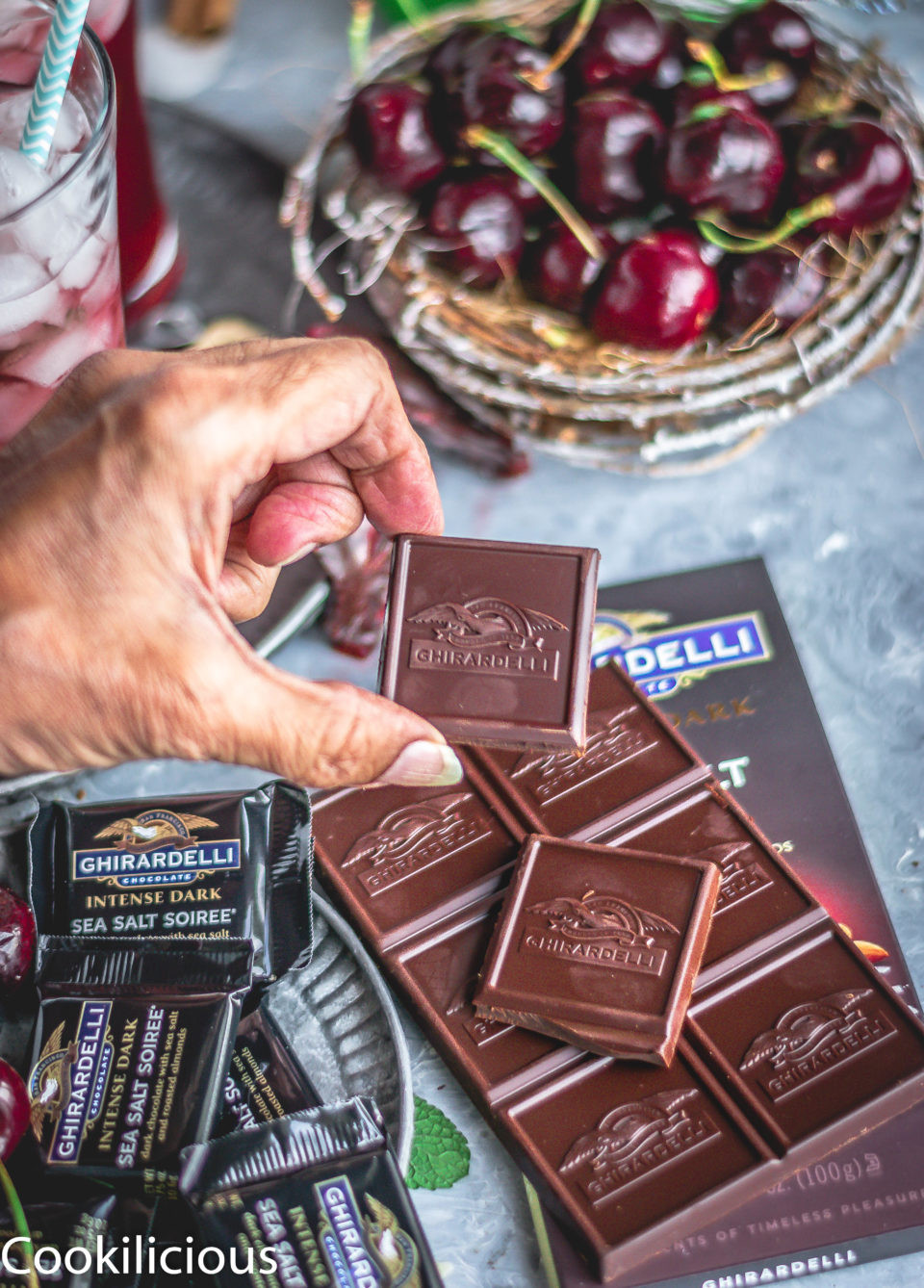 a hand holding a Ghirardelli Intense Dark chocolate bar