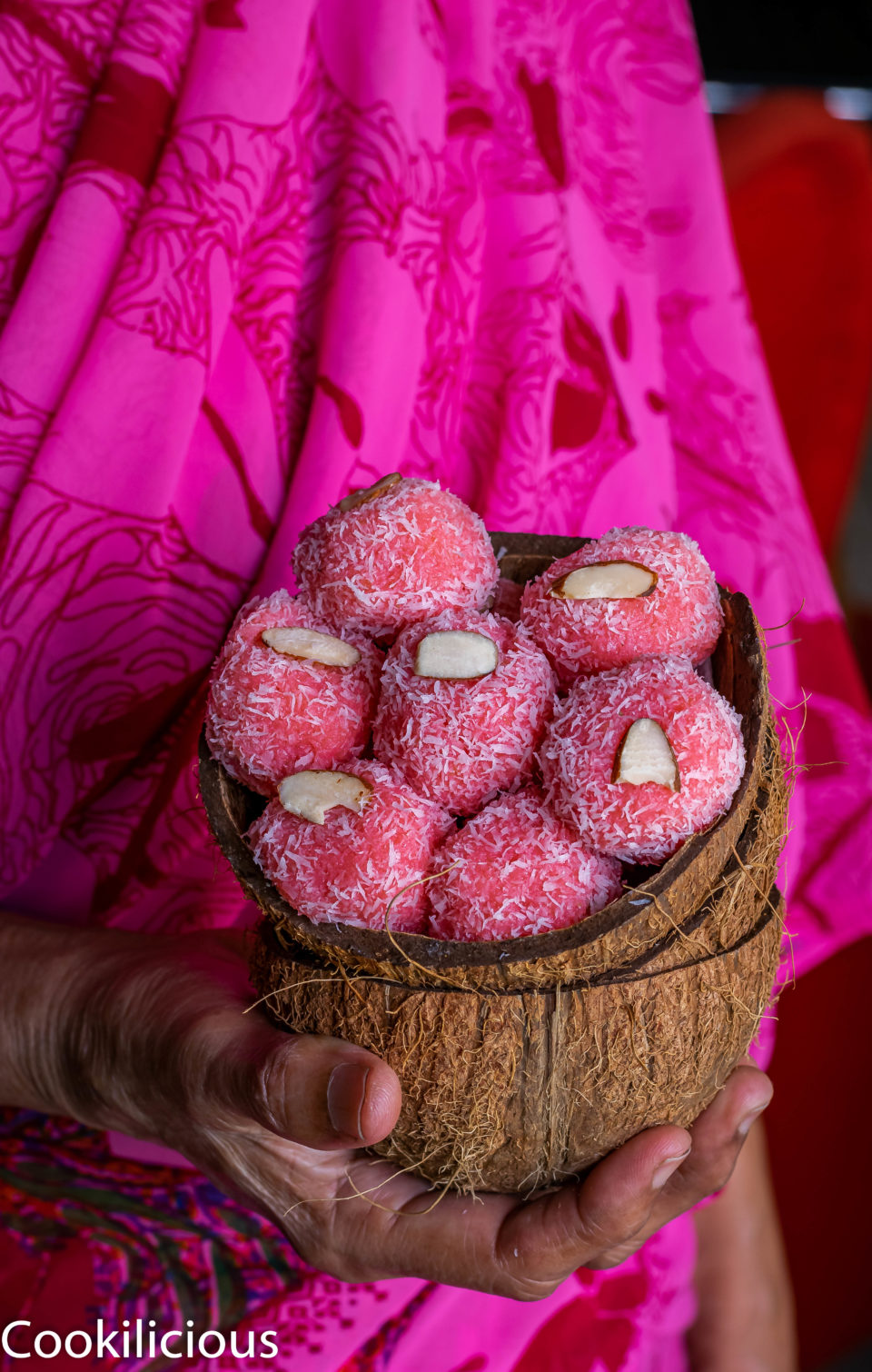 a hand holding Instant Rose & Coconut Ladoo in coconut shells