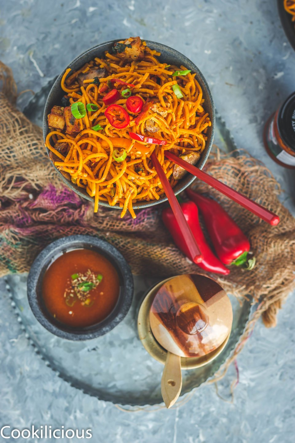 flat lay image of Asian Style Thai Basil Tofu Stir Fry Noodles in a bowl with chopsticks in it and a bowl of sauce next to it