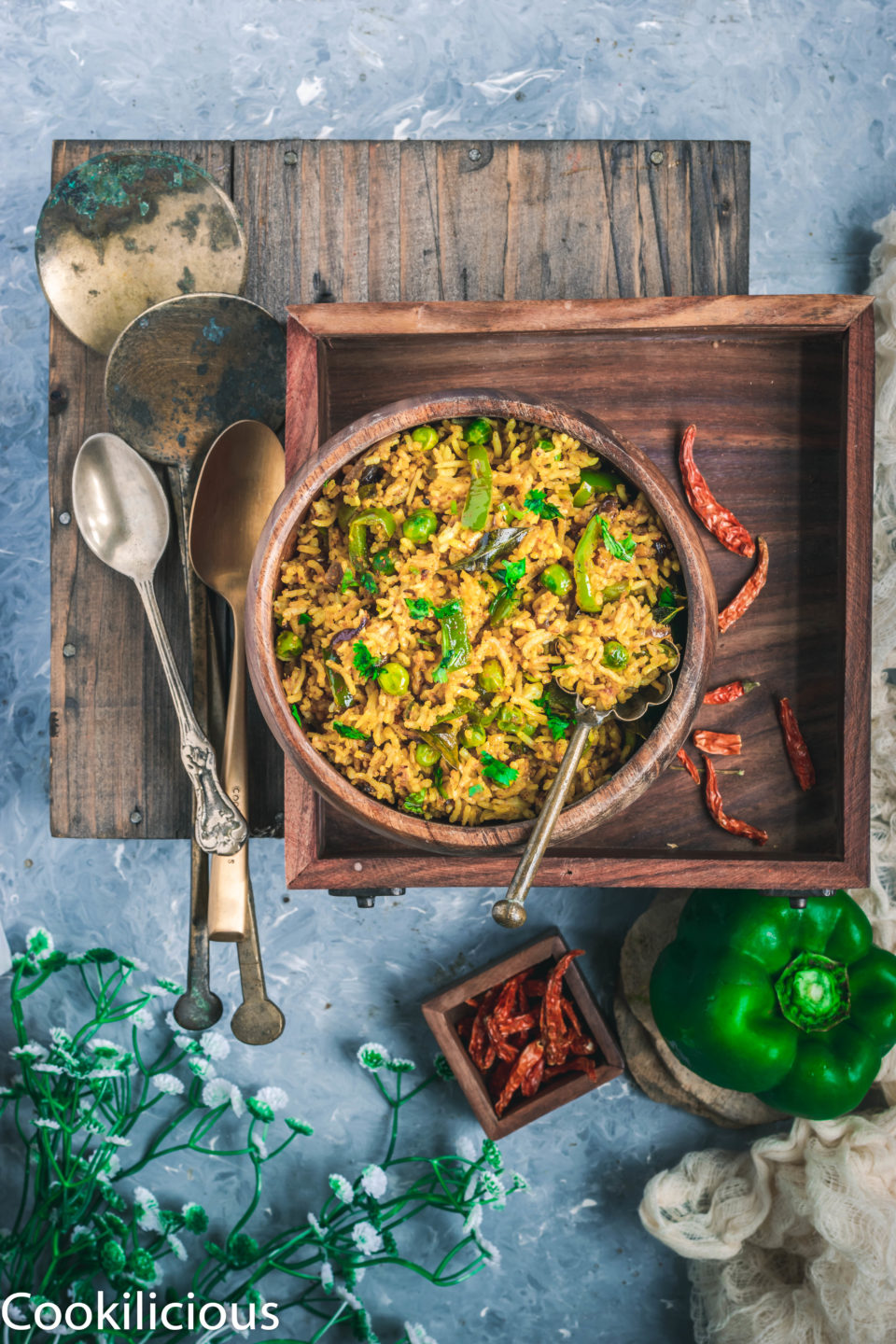 top angle shot of Bell Pepper Fried Rice in a wooden bowl placed over a wooden tray with a set of cutlery on the side
