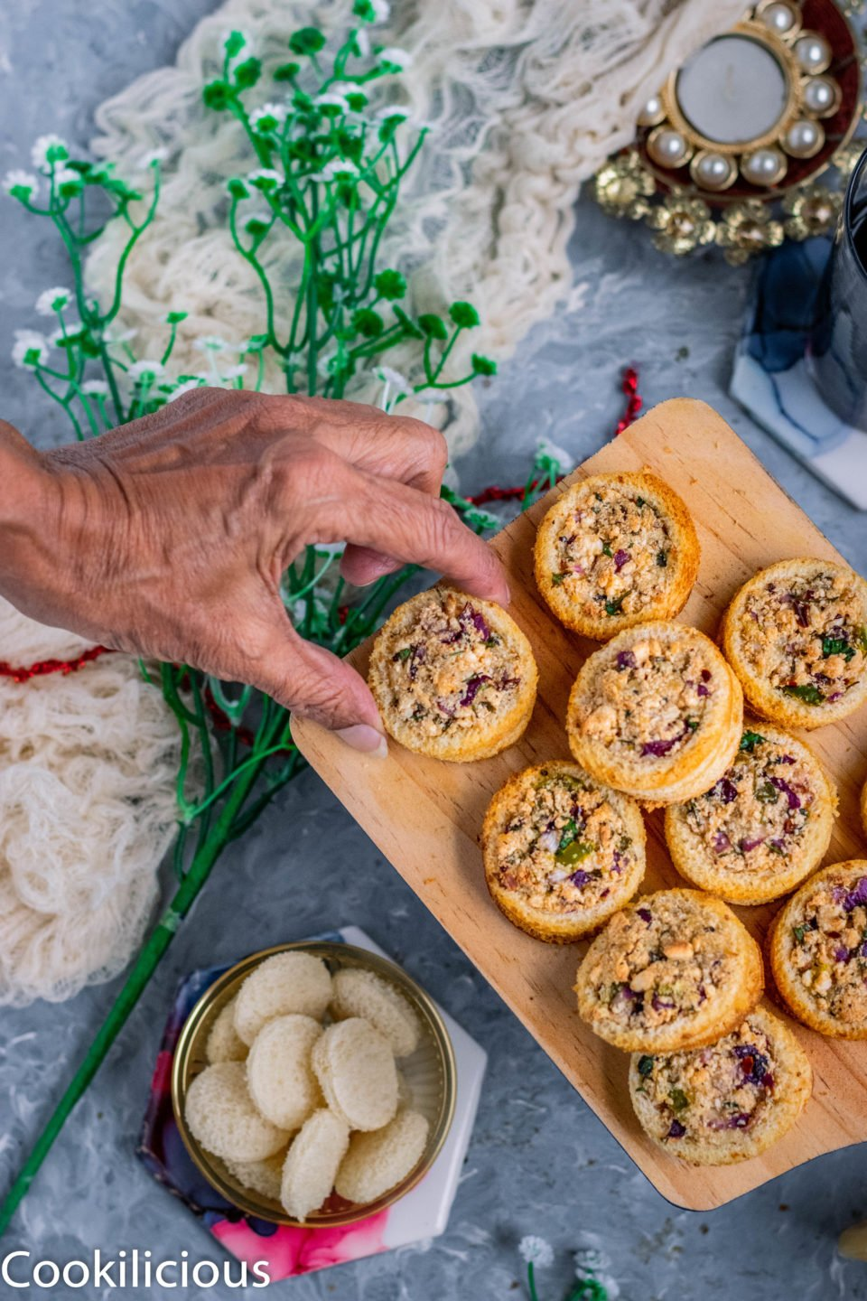 a hand reaching out to a pick up one Baked Cheese Stuffed Bread Ring from a wooden tray