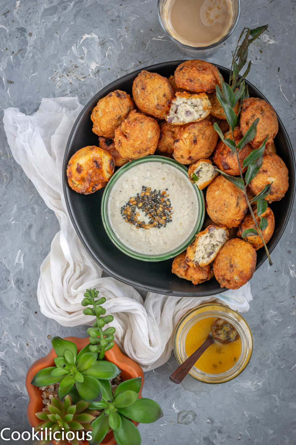 Dill Flavored Lentil Fritters in a platter with a curry leaf sprig on top