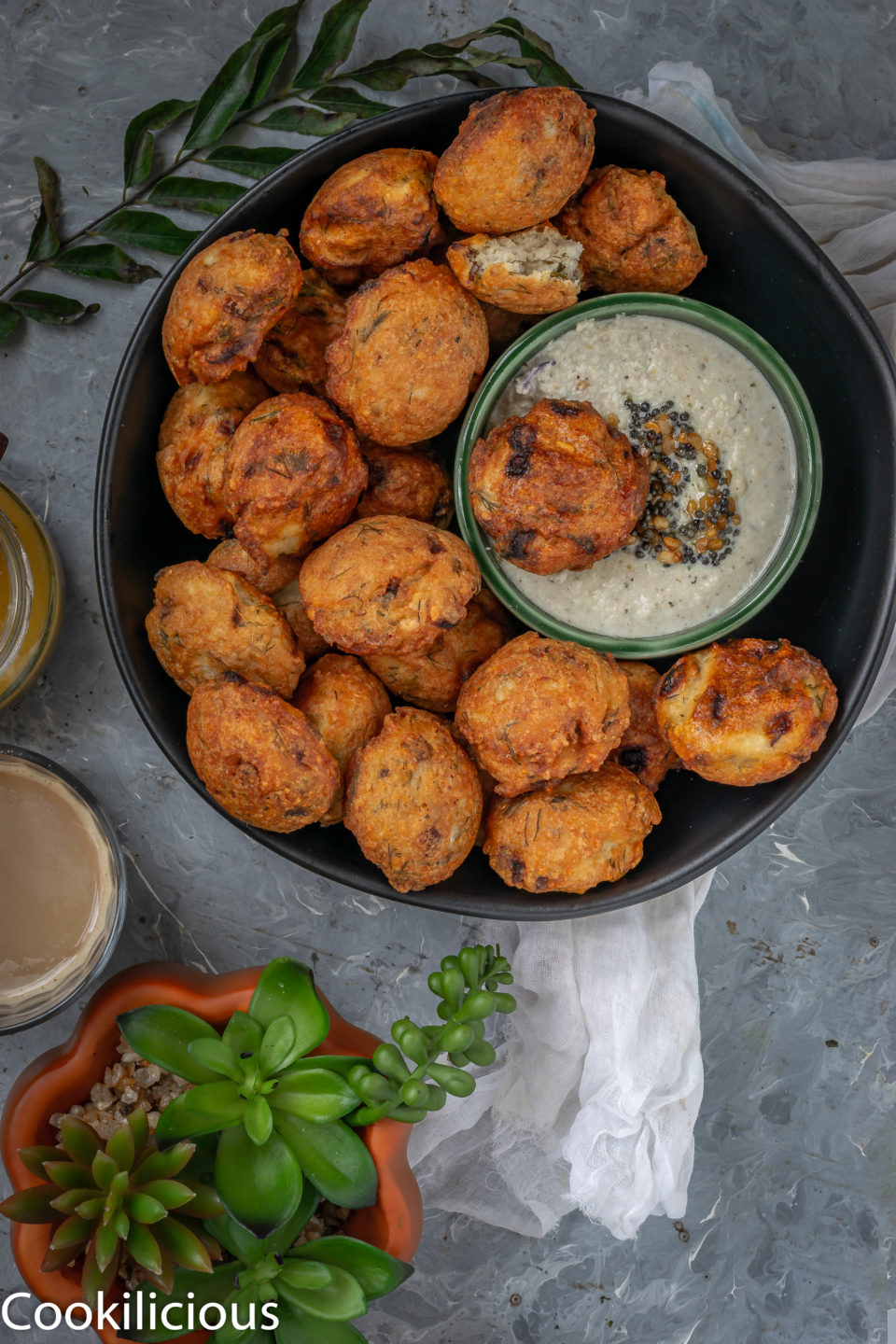 a small chutney bowl in a platter of Dill Flavored Lentil Fritters