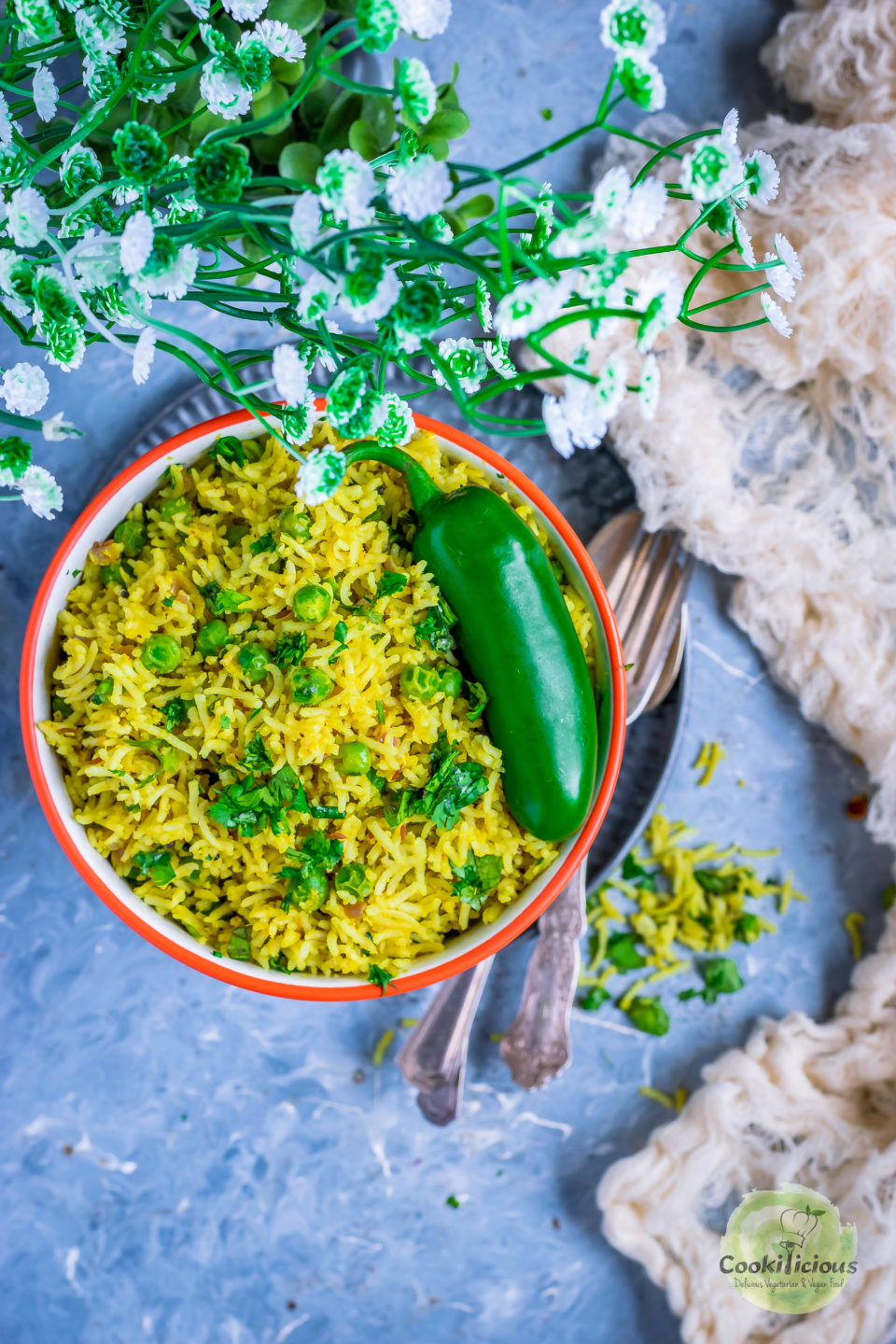 Green Peas Pulao in a bowl with a jalapeno on top and cutlery on the side