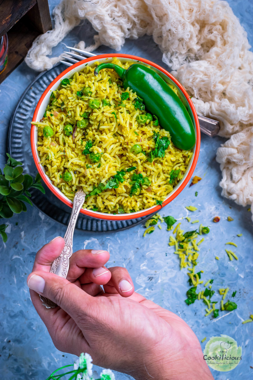a hand holding a spoon and digging into a bowl of Green Peas Pulao
