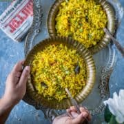 a set of hands holding a plate of tamarind poha