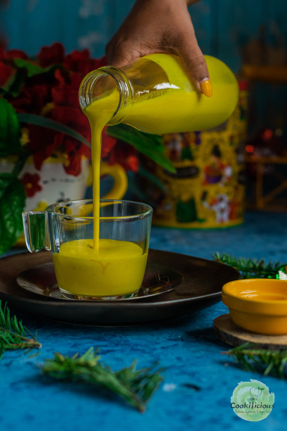 a hand pouring Iced Golden Milk from a bottle into a glass