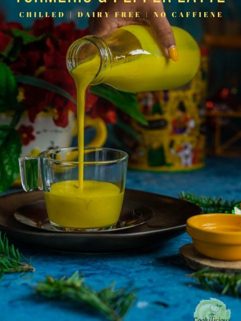 a hand pouring Iced Golden Milk from a bottle into a glass and text at the top