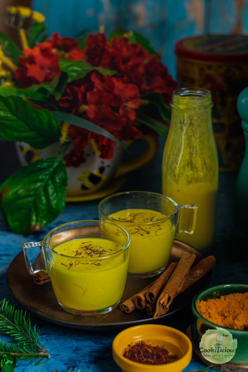 2 glasses of Iced Golden Milk with cinnamon sticks in it