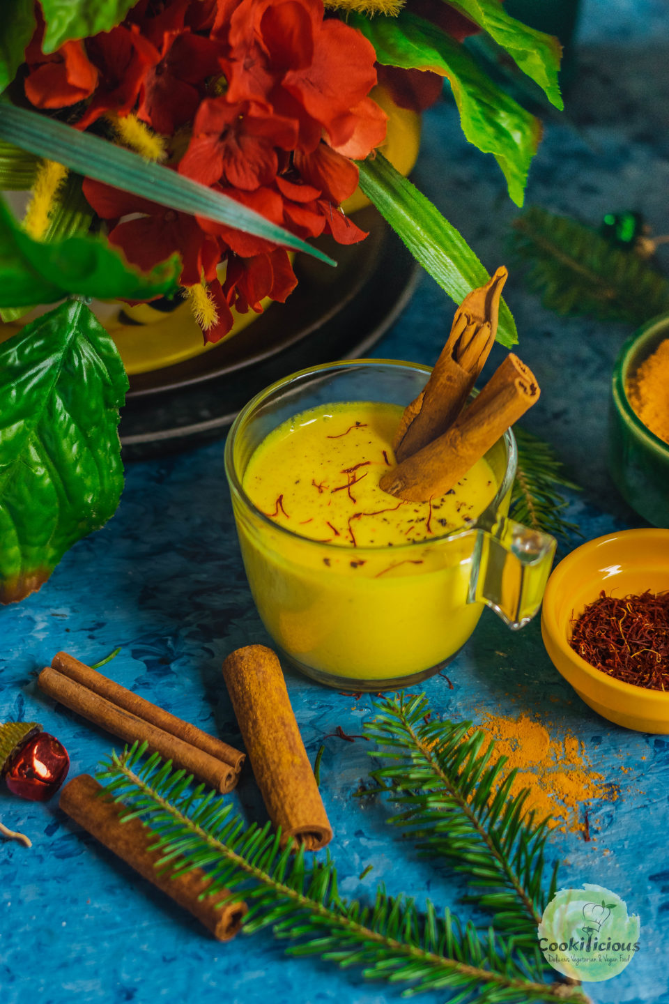one glass filled with Iced Golden Milk and 2 cinnamon sticks in it