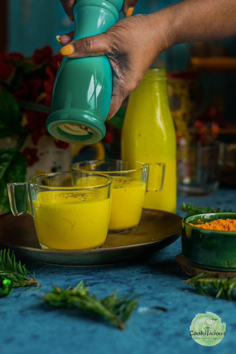 a hand adding freshly crushed pepper over a glass of Iced Golden Milk