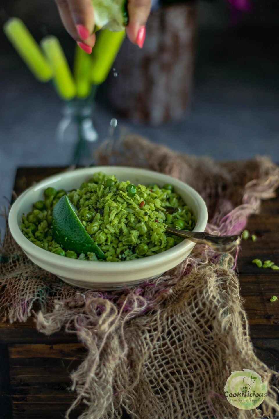 a hand squeezing lemon juice over a bowl of this plant-based snack poha (rice flakes)