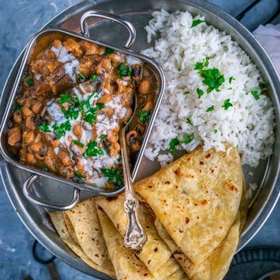 a plate filled with rice, roti and a bowl of Instant Pot Black Eyed Peas Chili