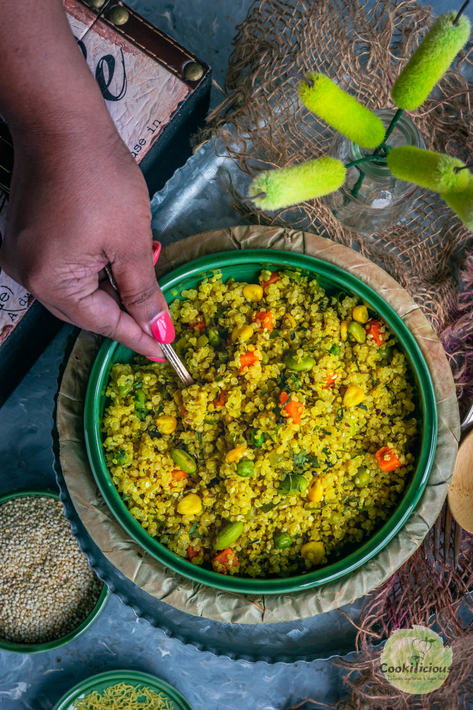 a hand holding a spoon digging into a bowl of Vegetable Quinoa Upma