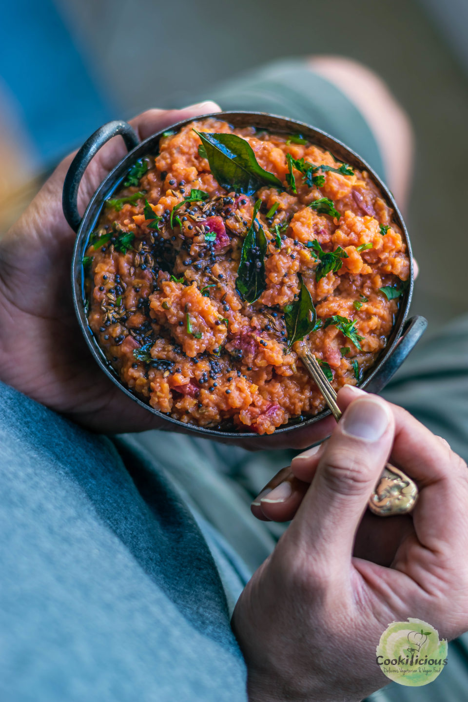 a pair of hands holding a bowl of Instant Pot Beetroot Rasam Rice