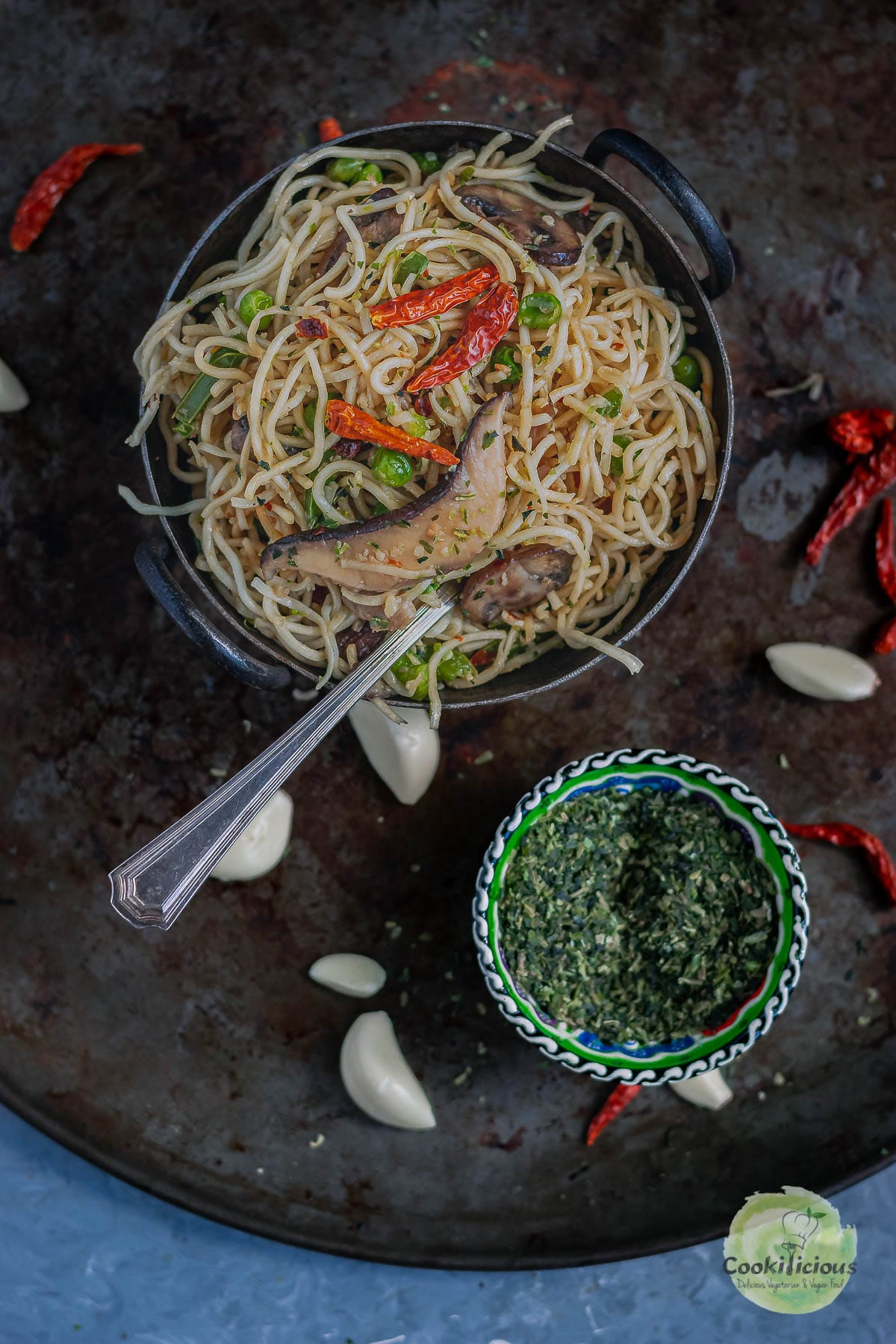 a bowl of Chilly Garlic Noodles next to a small bowl of parsley