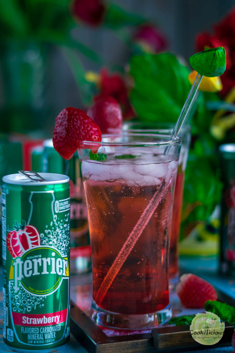 a slim can of Perrier® Flavors placed next to a glass of Strawberry Hibiscus Rose Punch