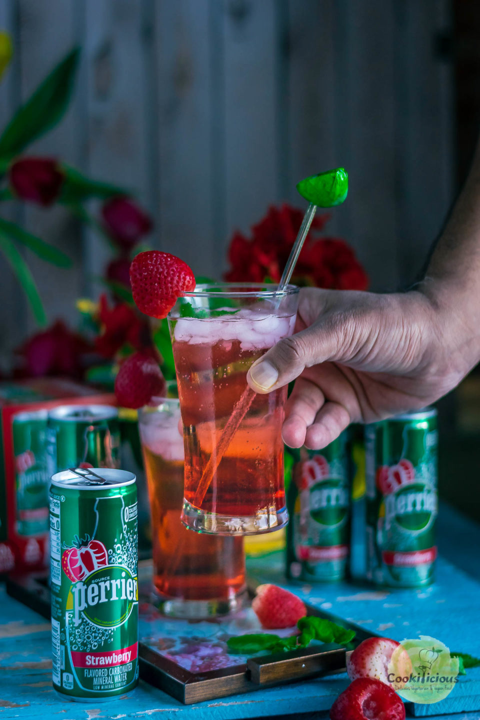 a hand lifting a glass filled with strawberry hibiscus rose punch