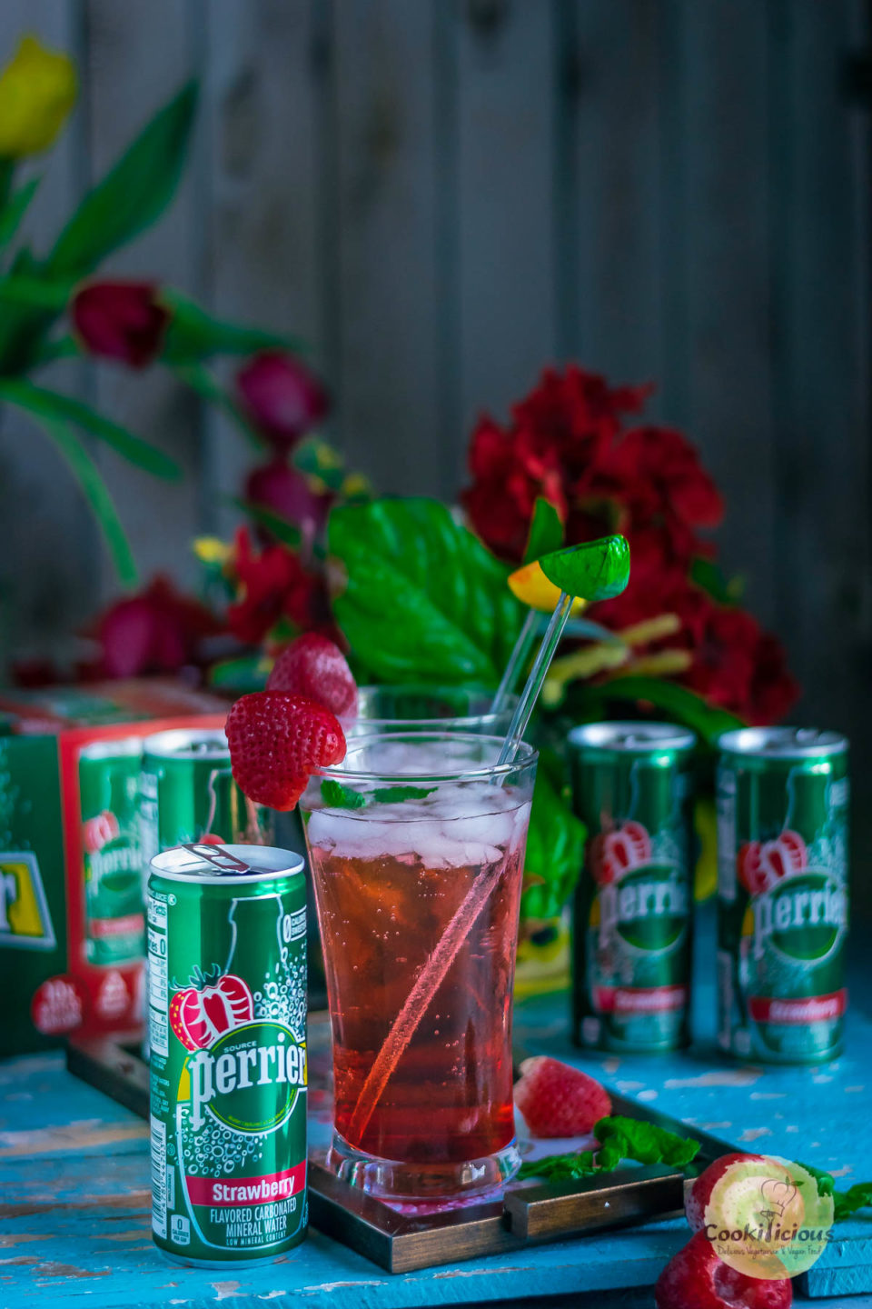 many cans of Perrier® Flavors around a glass of fruit punch