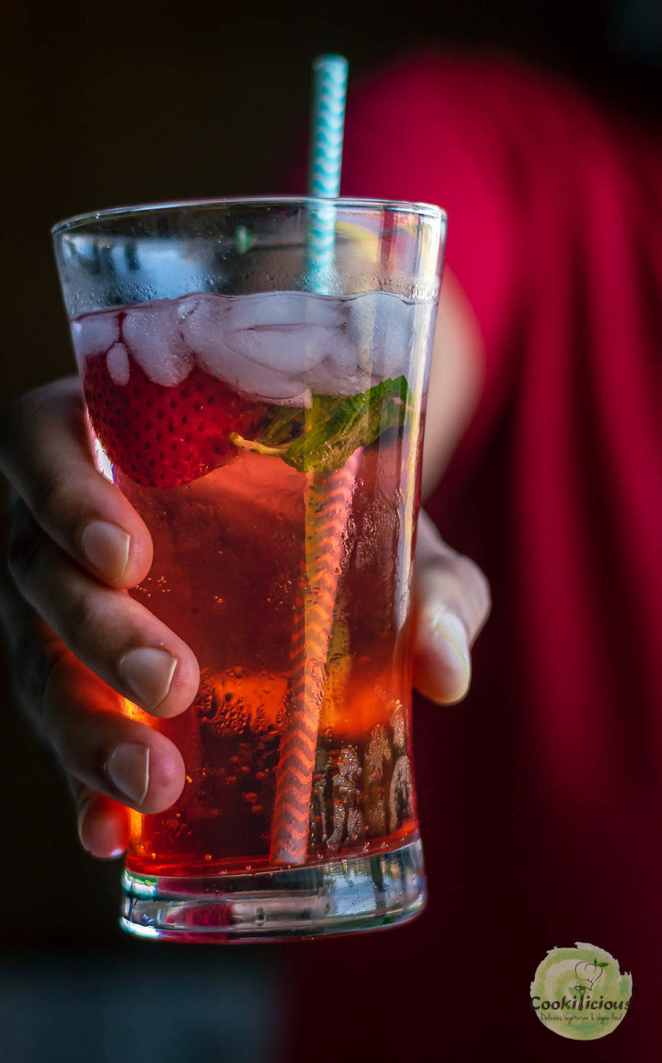 a hand holing a glass of Strawberry Hibiscus Rose Punch