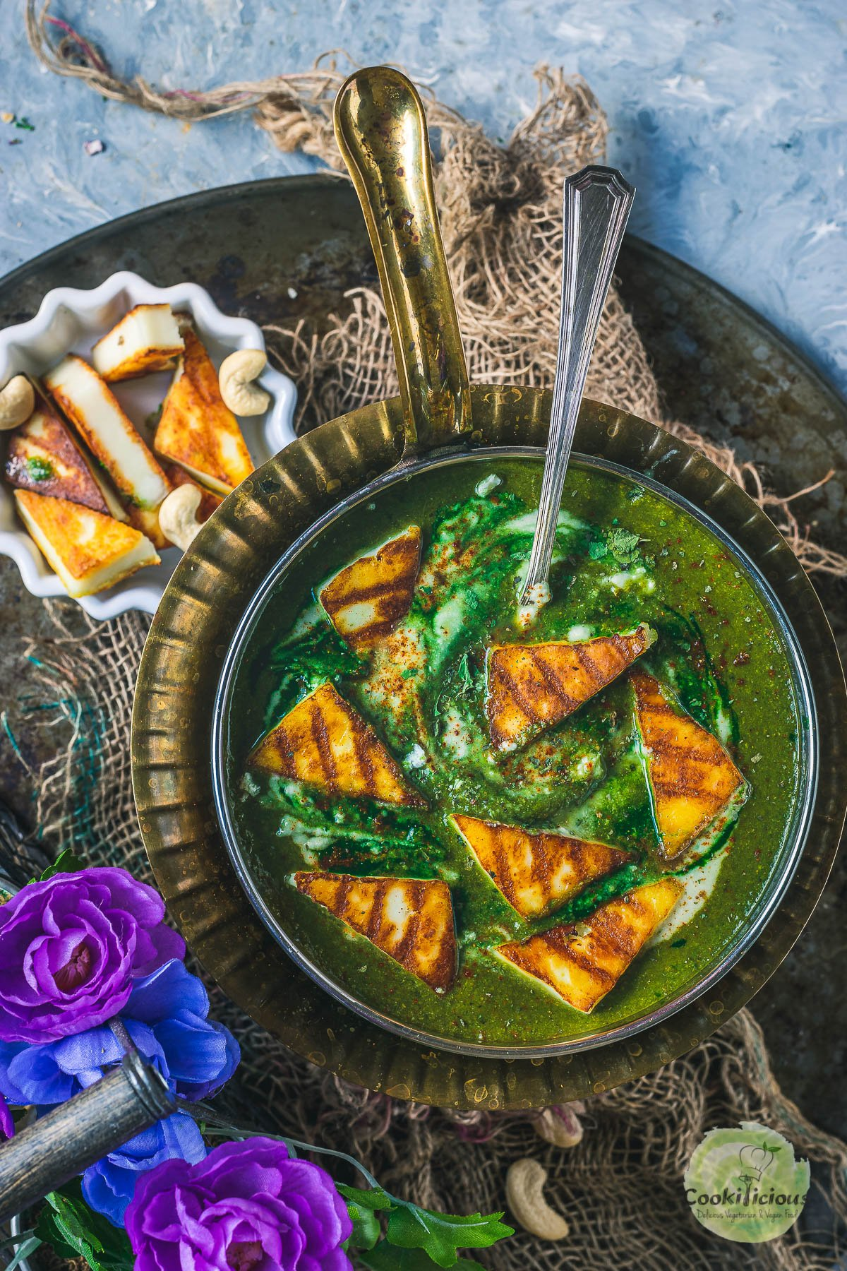 Restaurant Style Palak Paneer in a round platter with a spoon in it and some grilled paneer on the side