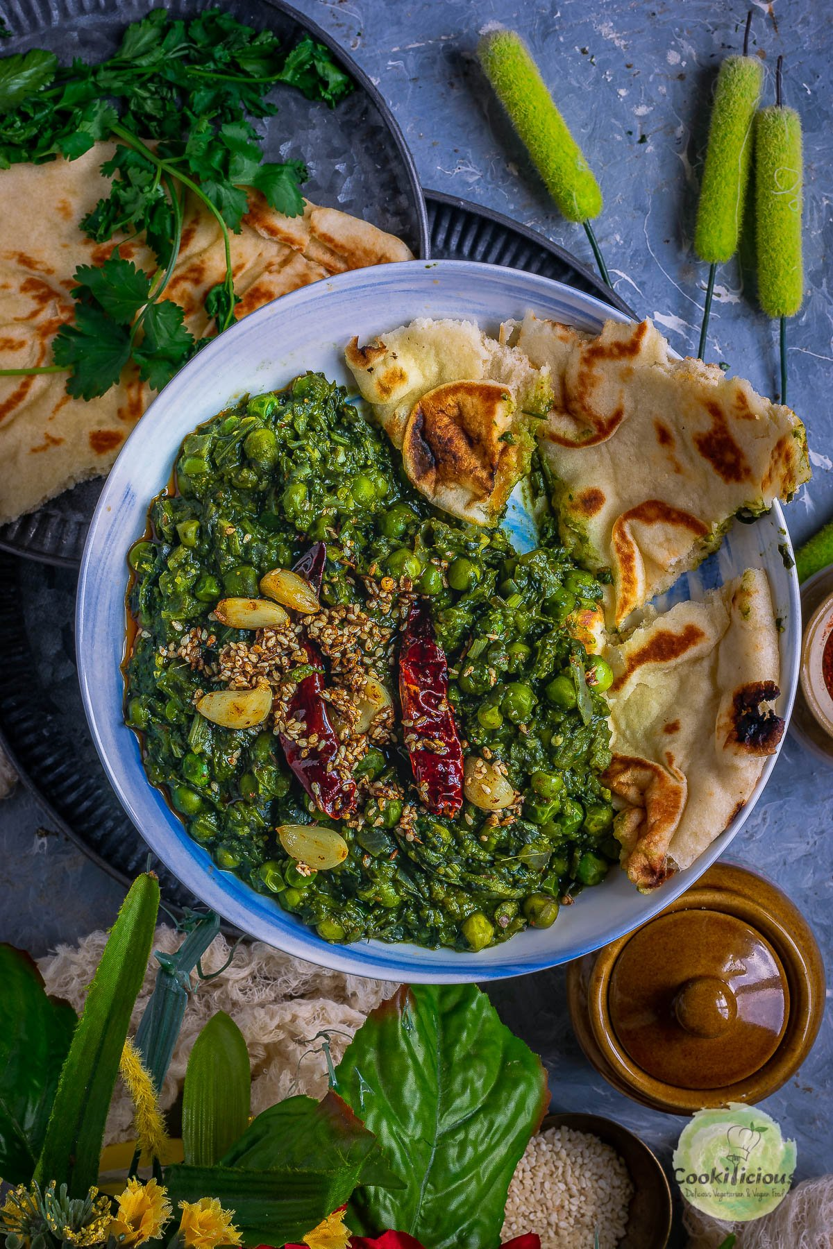 Garlicky Peas Spinach Fenugreek Curry with naan pieces in a round bowl