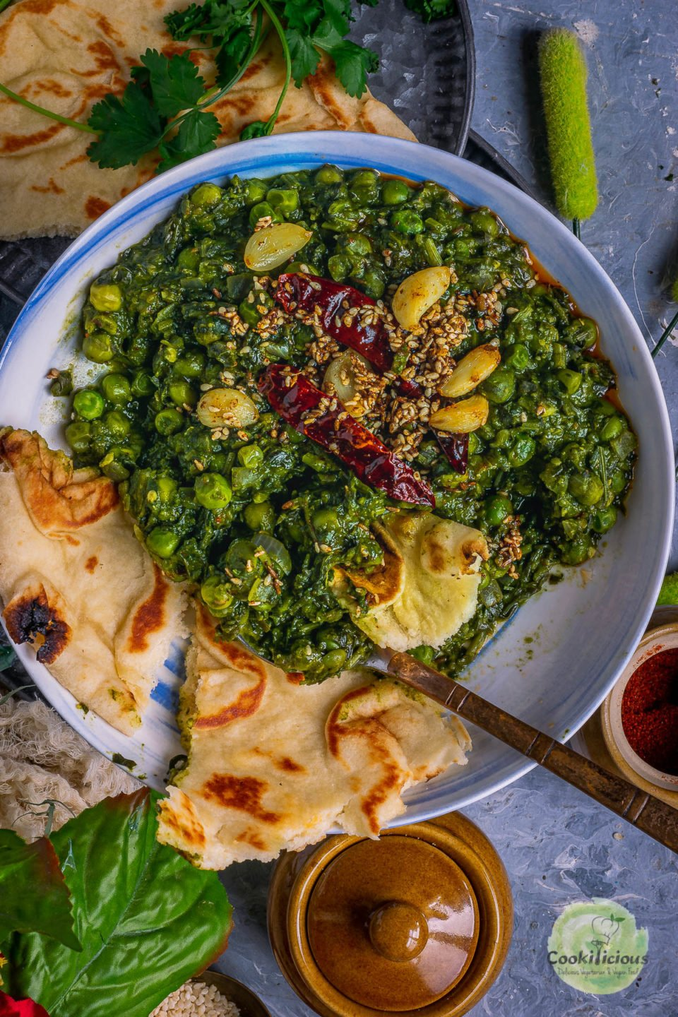 a round bowl filled with Garlicky Peas Spinach Fenugreek Curry and naan pieces