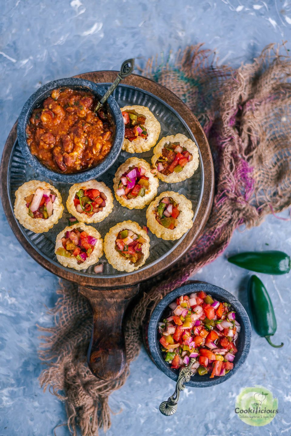 a round plate filled with Indian Mexican Pani Puri along with a bowl of beans in tomato sauce and next to it is a bowl of salsa