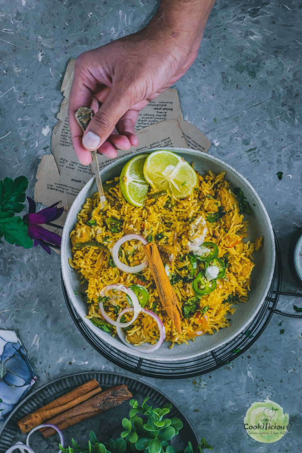 a hand reaching out with a spoon in hand to dig in to a bowl of Soya Chunks Pulao