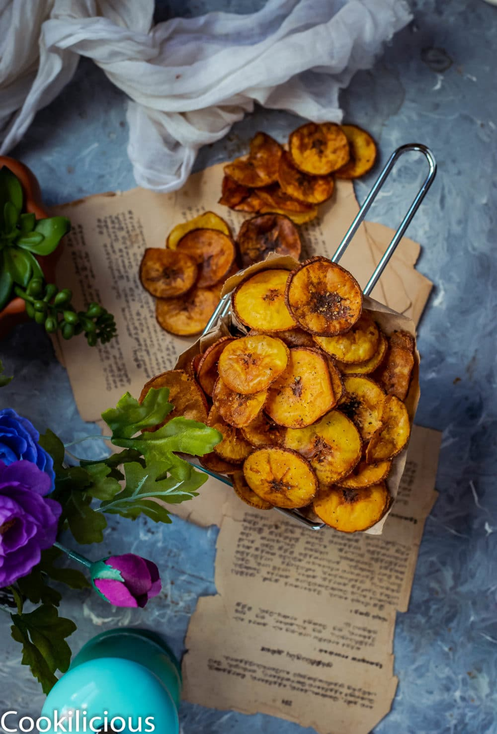 Fried Raw Banana Vegan Chips served in a basket with some fallen next to it