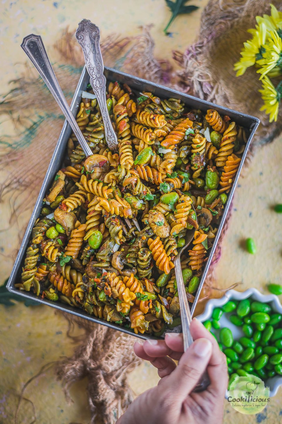 a hand digging into a platter of Indian Pasta Recipe | One-Pot Vegan Curry Pasta Dish with a spoon