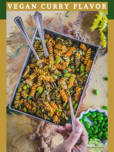 a hand digging into a platter of Indian Pasta Recipe | One-Pot Vegan Curry Pasta Dish with a spoon and text at the top