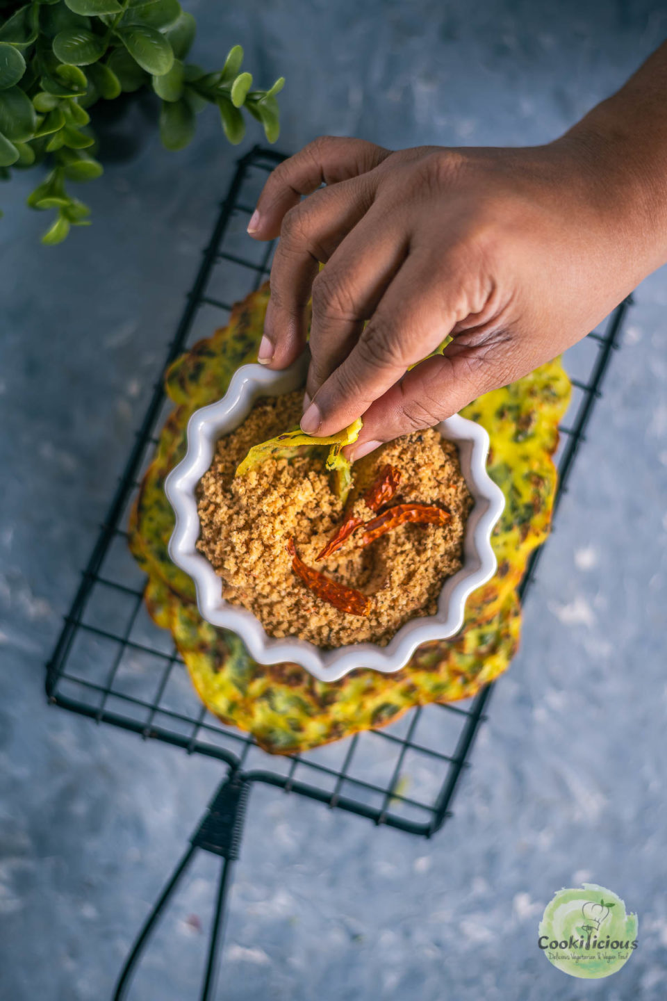 a hand holding a piece of methi ghavan and digging into a bowl of peanut chutney