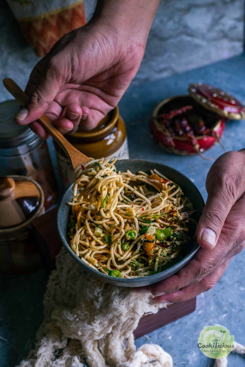 a hand digging taking a forkful of Hot and Spicy Noodles/ Cilantro Pot Noodles from a bowl