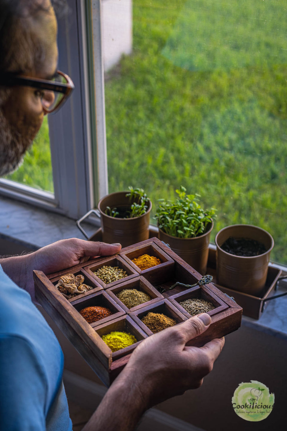 A man holding a spice box containing coriander cumin powder