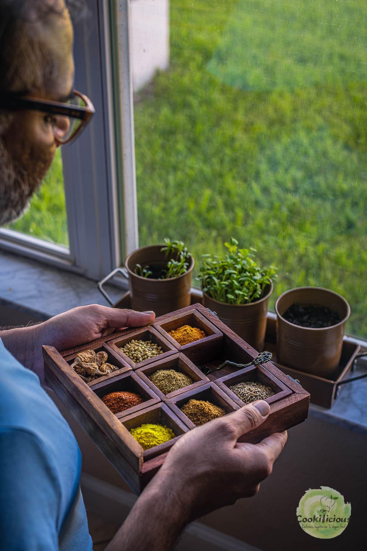 A man holding a spice box containing coriander cumin powder